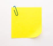 Foglio di carta giallo con la graffetta blu su un fondo bianco Fotografia Stock Libera da Diritti