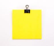 Foglio di carta giallo con la graffetta nera su un backgroun bianco Fotografia Stock Libera da Diritti