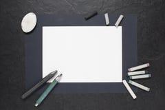 Foglio di carta i rifornimenti della pittura e sulla tavola Immagini Stock