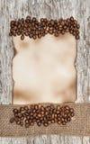 Foglio di carta invecchiato con i chicchi di caffè ed il nastro della tela da imballaggio Fotografie Stock