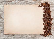 Foglio di carta invecchiato con i chicchi di caffè sul vecchio legno fotografia stock libera da diritti