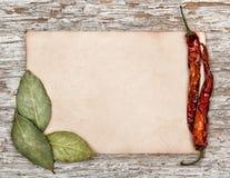 Foglio di carta invecchiato con le foglie ed il pepe asciutti della baia Fotografia Stock Libera da Diritti