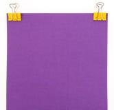 Foglio di carta porpora con la graffetta gialla su un backgrou bianco Fotografie Stock Libere da Diritti