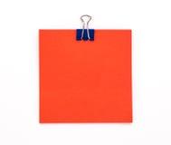 Foglio di carta rosso con la graffetta blu su un fondo bianco Immagini Stock Libere da Diritti