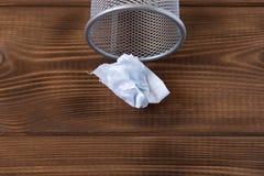 Foglio di carta sgualcito il canestro del metallo e Su una priorit? bassa di legno fotografie stock libere da diritti