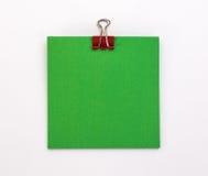 Foglio di carta verde con la graffetta rossa su un fondo bianco Immagine Stock Libera da Diritti