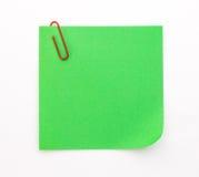 Foglio di carta verde con la graffetta rossa su un fondo bianco Fotografie Stock Libere da Diritti