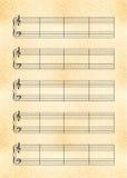 Foglio giallo di dimensione A4 di vecchia carta con la doga della nota di musica con la chiave tripla e bassa Fotografia Stock