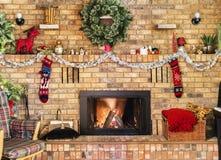Fogo acolhedor na chaminé do tijolo e envoltório decorado para o Natal Foto de Stock
