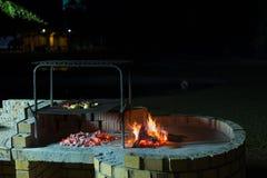 Fogo ardente do acampamento no crepúsculo no local de acampamento, preparando-se para o assado ou o braai, fora atividade em Áfri Fotos de Stock Royalty Free