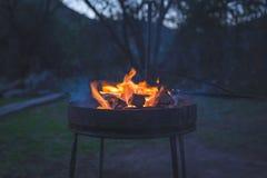 Fogo ardente do acampamento no crepúsculo no local de acampamento, preparando-se para o assado ou o braai, fora atividade em Áfri Foto de Stock