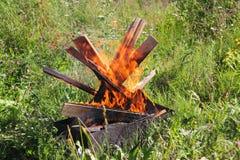 Fogo da madeira e das placas com os pregos na grama verde imagens de stock