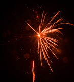 Fogo de artifício alaranjado bonito na véspera de anos novos Imagens de Stock