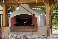 Fogão de pedra tradicional velho do forno do pão com o fogo de madeira de queimadura Imagens de Stock Royalty Free