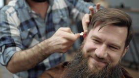Fogo do uso do barbeiro com homens adultos com uma barba longa no cabeleireiro do ` s dos homens Preparando a barba Cabeleireiro  filme