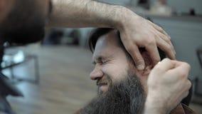Fogo do uso do barbeiro com homens adultos com uma barba longa no cabeleireiro do ` s dos homens Preparando a barba Cabeleireiro  vídeos de arquivo