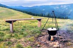 Fogo e jogador de acampamento dos turistas com alimento imagem de stock royalty free