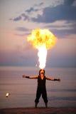 Fogo-respiração impressionante na praia no por do sol Fotografia de Stock