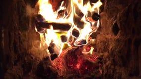 Fogo vermelho bonito da madeira da fatia, carvões pretos cinzentos escuros dentro do soldador do metal filme
