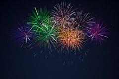 Fogos-de-artifício alaranjados roxos do verde azul sobre o céu estrelado Imagens de Stock Royalty Free