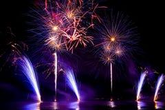 Fogos-de-artifício brilhantemente coloridos disparados sobre o mar Fotografia de Stock Royalty Free