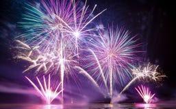 Fogos-de-artifício brilhantemente coloridos disparados sobre o mar Imagem de Stock