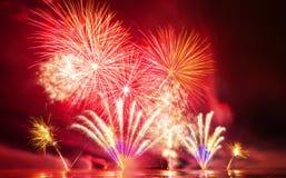 Fogos-de-artifício brilhantemente coloridos disparados sobre o mar Foto de Stock Royalty Free