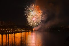 Fogos-de-artifício brilhantes coloridos, saudação de cores douradas no céu noturno com reflexão no lago Fundo abstrato do feriado Fotos de Stock