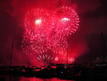 Fogos-de-artifício carmesins com as estrelas brilhantes no porto Fotografia de Stock
