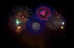 Fogos-de-artifício coloridos em uma noite do feriado fotografia de stock