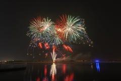 Fogos-de-artifício coloridos que explodem sobre um céu noturno escuro imagens de stock