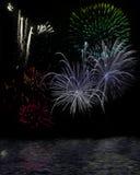 Fogos-de-artifício distantes sobre a água Fotografia de Stock Royalty Free