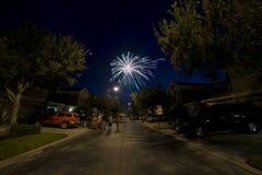 Fogos-de-artifício do feriado em fogos-de-artifício coloridos de uma rua residencial foto de stock royalty free