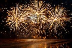 Fogos-de-artifício dourados bonitos sobre o mar no fundo do céu noturno Imagens de Stock
