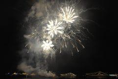 Fogos-de-artifício e faíscas na noite sobre o mar imagens de stock royalty free