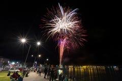 Fogos-de-artifício estalando no céu noturno sobre um porto imagem de stock royalty free