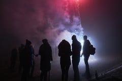 Fogos-de-artifício estando e de observação dos povos, silvester, obscuridade, silhueta Imagem de Stock Royalty Free