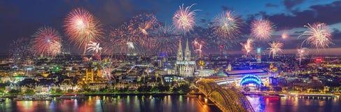 Fogos-de-artifício na skyline da água de Colônia com catedral e Hohenzollern Bri fotografia de stock royalty free