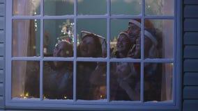 Fogos-de-artifício de observação da família feliz através da janela video estoque