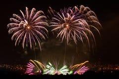 Fogos-de-artifício Sparkles grandes acima da cidade da noite Fotografia de Stock