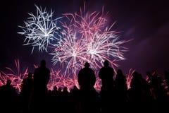 Fogos-de-artifício grandes com observação mostrada em silhueta dos povos Fotografia de Stock Royalty Free