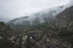 Fogs Among Trees, Dam, and Mountains on a Rainy Day in Hetch Hetchy Reservoir Area in Yosemite National Park, California. Hetch Hetchy is the name of a valley, a Royalty Free Stock Image