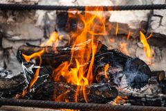 A fogueira, em que o alimento é fritado, no espeto, queimaduras com uma chama alaranjada bonita imagem de stock royalty free