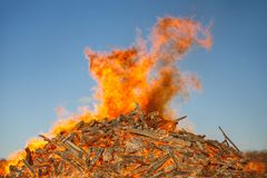 Fogueira enorme de queimadura contra o céu azul fotografia de stock