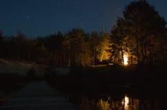 Fogueira na ponte de madeira da floresta da noite sobre o rio que conduz nas madeiras imagens de stock