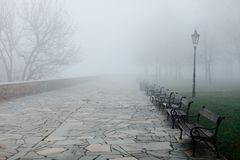 Fogymorgen im Park, Bänke verschwinden in der niedrigen Sicht lizenzfreies stockfoto
