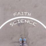 Foi contre le texte de la science sur l'au sol, les pieds et les chaussures d'asphalte sur le plancher image libre de droits