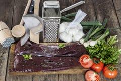 Foie et légumes crus avec la vaisselle de cuisine Photo stock