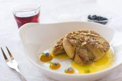 Foie Gras med Apple sås på den vita plattan royaltyfri bild