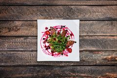 Foie gras salad with wild berry sauce. Foie gras salad with wild berry sauce, served on the white plate with wooden background. top view Royalty Free Stock Images